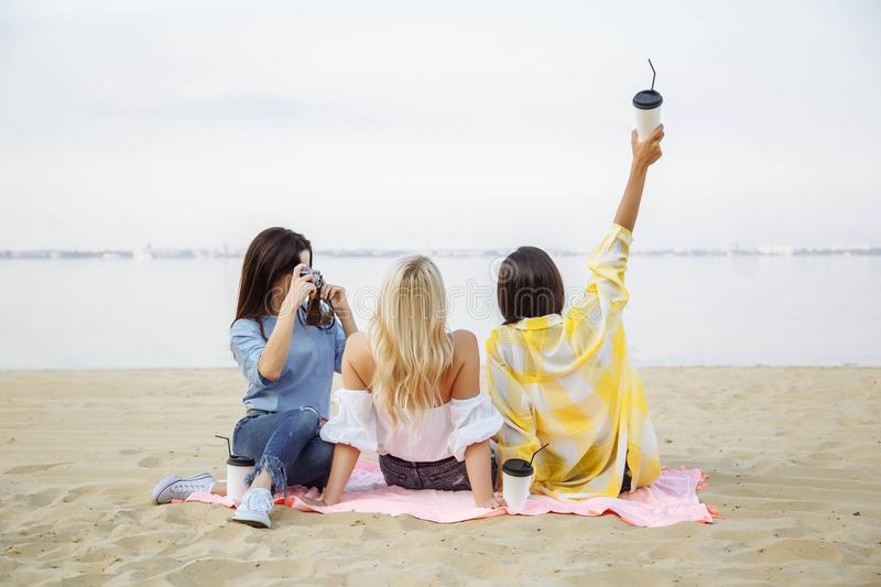 Group of girls friends take photos on the beach. stock photography