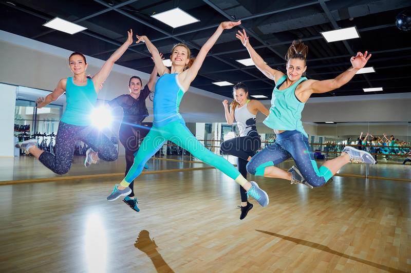 A group of girls jump with smiles in the gym royalty free stock photography