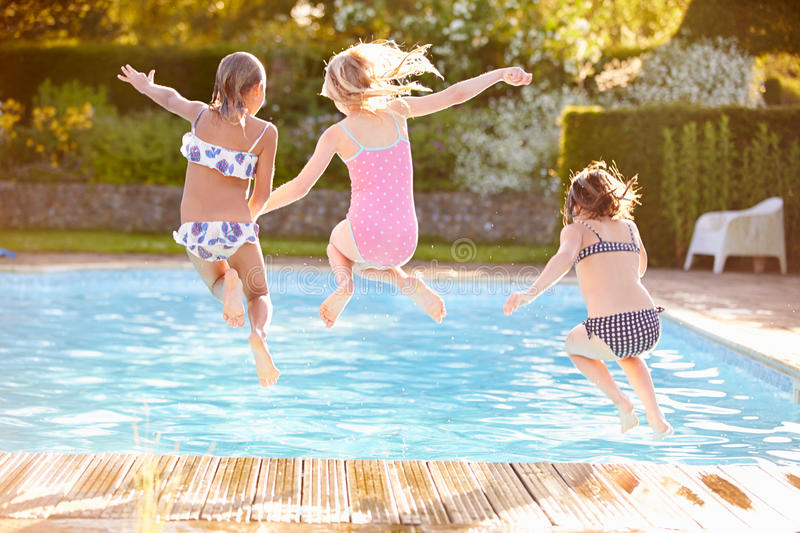 Group Of Girls Jumping Into Outdoor Swimming Pool stock photo