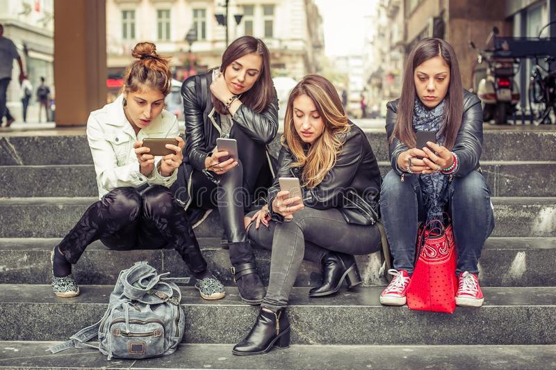 Group of girls sitting on the city stairs with smartphone royalty free stock images