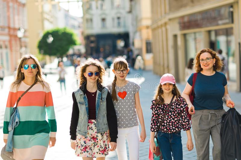 Group of girls walking through downtown - shopping trip. Group of girls walking through downtown, mothers and daughters together on a shopping trip royalty free stock image