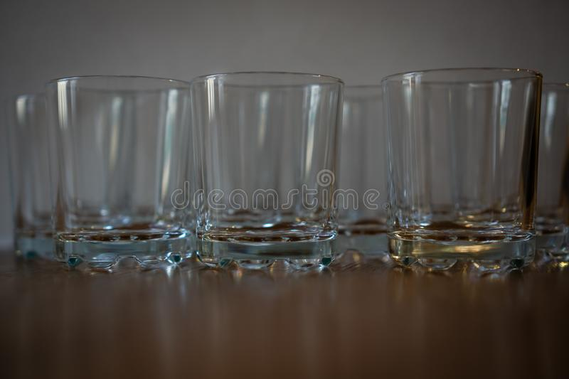 A group of glasses made of glass stands on a wooden surface. The glasses are empty, clean. Horizontal orientation royalty free stock photo