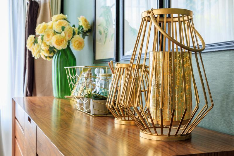 Group of golden decoration on the drawer in bedroom. Golden lamps and ornamental plants in a pot and glass jar in a basket with frameon a wooden drawer by the royalty free stock photos