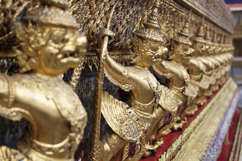 Golden Garuda statue stand around , the bronze symbol of Thai government, giant ancient gold eagle with crown sculpture. Group of golden Garuda statue stand royalty free stock images