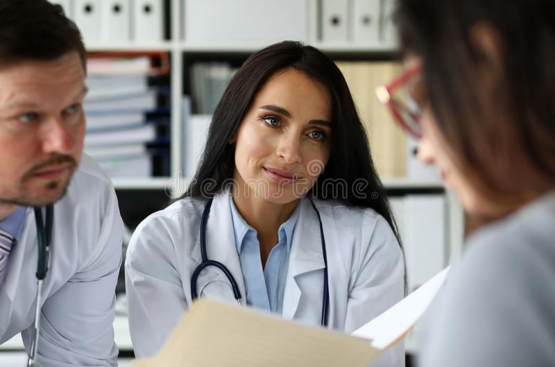 Group of GP consulting young woman in office royalty free stock photos