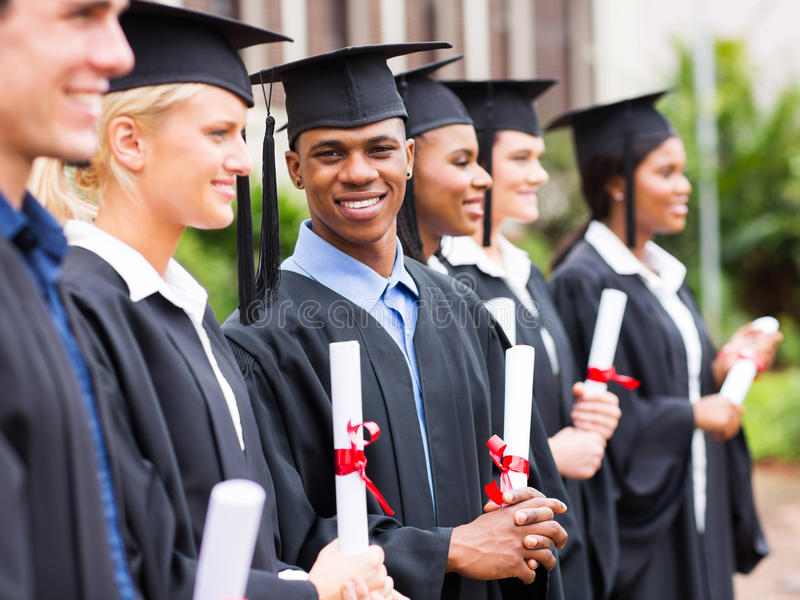 Group of graduates in library. Group of happy graduates holding diploma in library royalty free stock photo