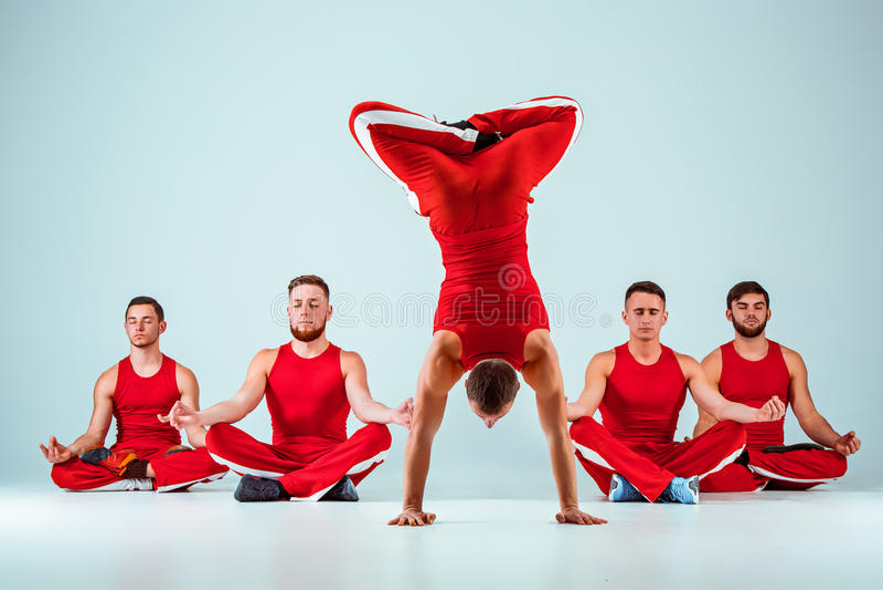 The group of gymnastic acrobatic caucasian men on balance pose. The group of gymnastic acrobatic caucasian men posing in balance posture on gray studio stock photo