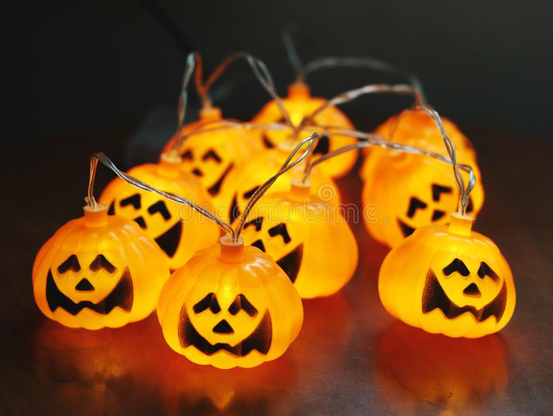 Group of Halloween pumpkin string lights glowing on the table for Halloween party decoration stock photos