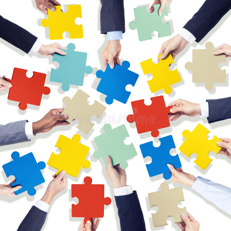 Group of Hands Holding Colorful Jigsaw Pieces.  royalty free stock photography