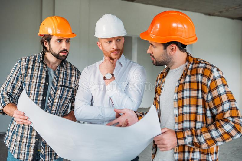 Group of handsome architects with blueprint having conversation inside of. Constructing building stock images