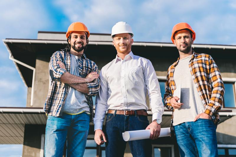 Group of handsome architects in front of. Construction site stock photography