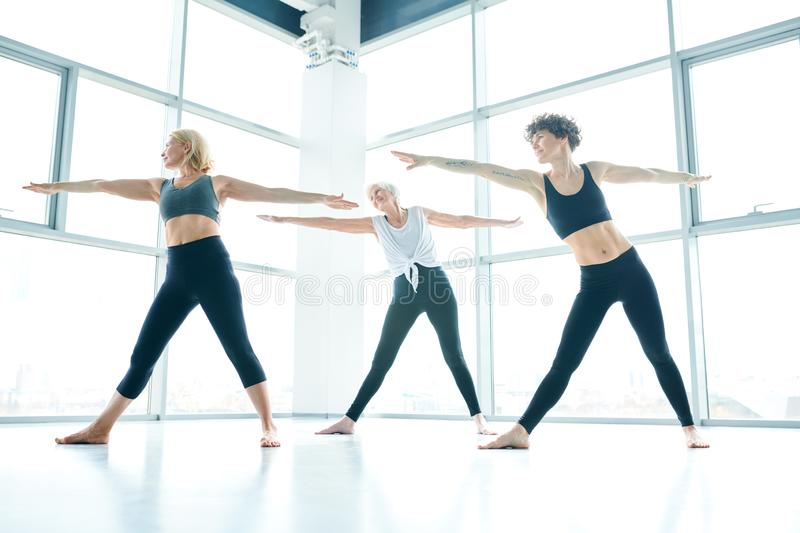 Sporty women. Group of happy actve females in activewear outstretshing their arms and legs while exercising during workout in fitness center stock images