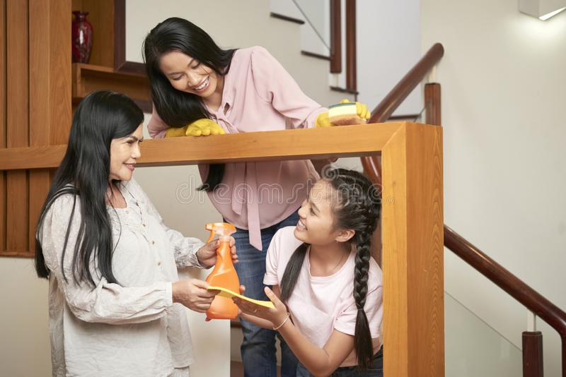 Cheerful multi-generational women cleaning house stock photo