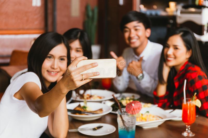 Group of Happy Asian male and female friends take selfie photo and have a social toast in restaurant royalty free stock photos