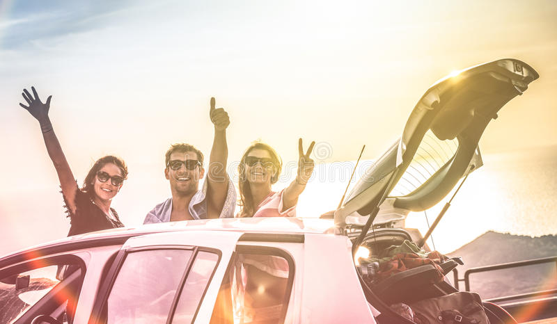 Group of happy best friends cheering on car road trip at sunset stock images