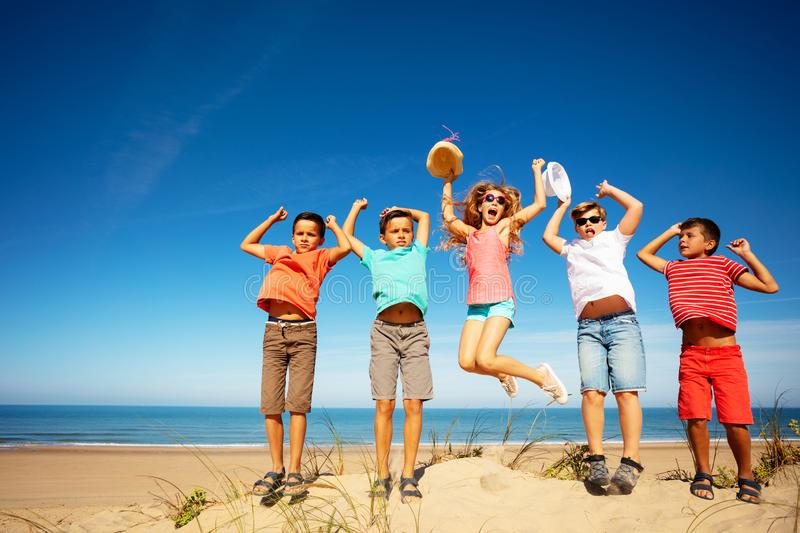 Group of happy boys and girls jump on sand beach royalty free stock photos