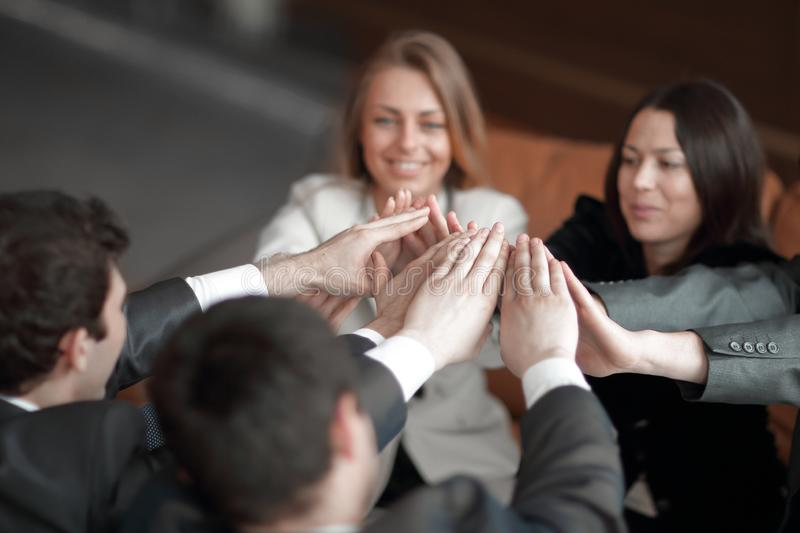 Group of happy business people holding hands together while sitting around the desk stock photos