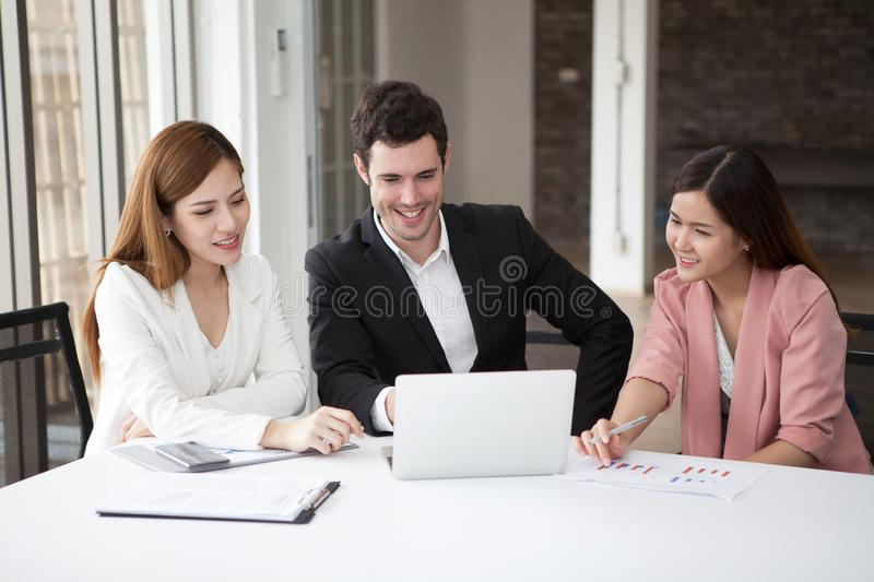 Group of happy business people men and woman working together on laptop in meeting room.teamwork of two girl asian and caucasian royalty free stock photography