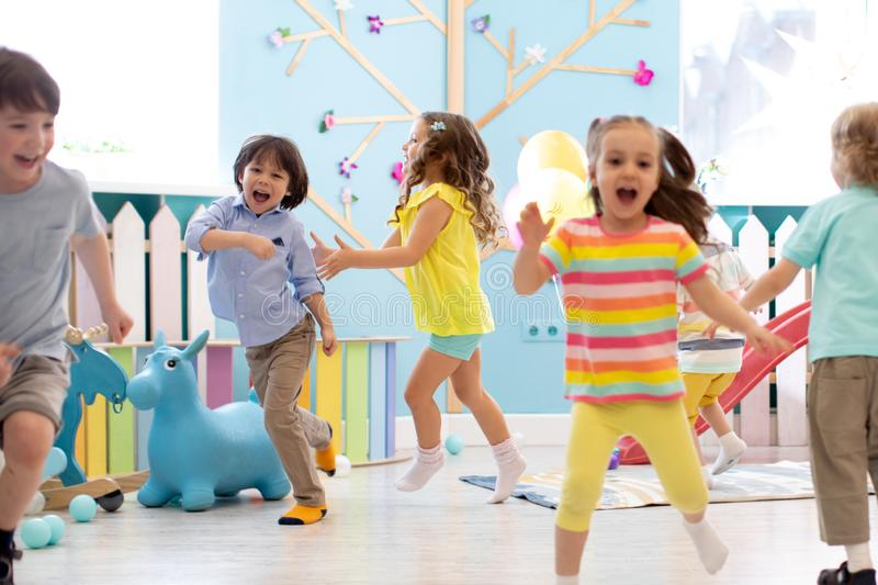 Group of happy children of boys and girls run in day care. Kids play in kindergarten royalty free stock photos