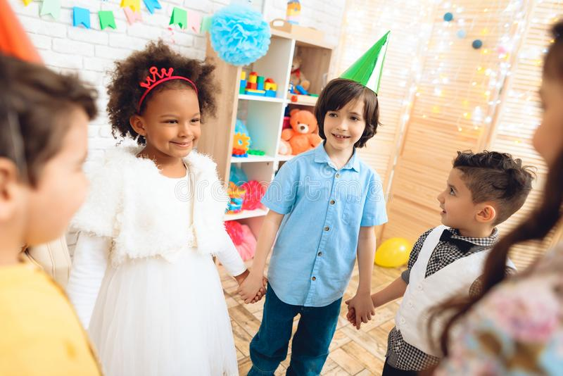 Group of happy children dancing round dance on birthday party. Concept of children`s holiday. Happy children have fun on celebration royalty free stock photo