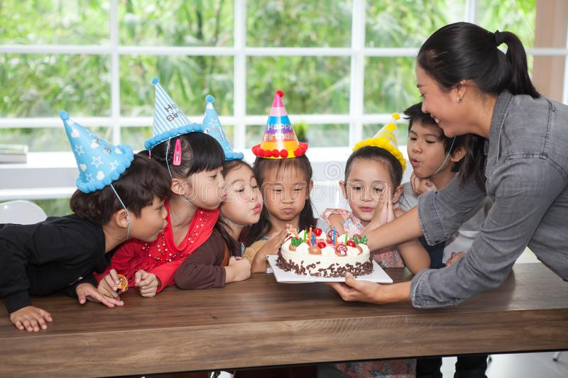 group of happy children girl with hat blowing candles on  birthday cake together celebrating in  party . kids gathered around royalty free stock photography