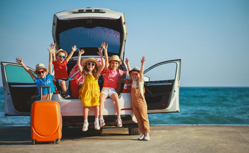 Group happy children girls and boys friends   on   car ride to summer trip stock images