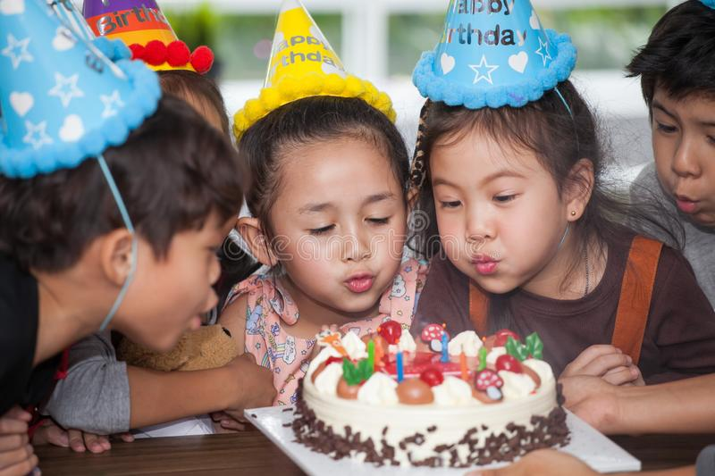 group of happy  children with hat blowing candles on  birthday cake together celebrating in party . adorable kids gathered around royalty free stock image