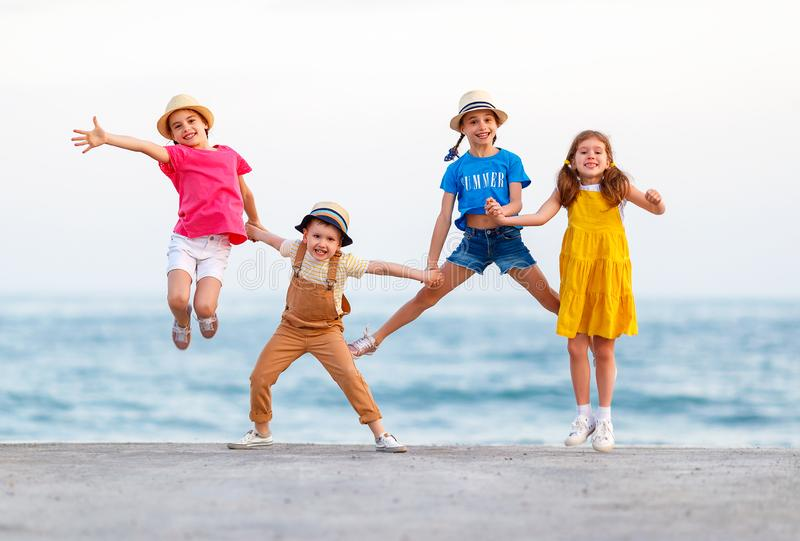 Group of happy children jump by   sea in summer stock photography