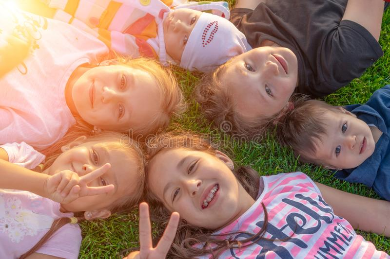 A group of happy children are lying in the park on the green grass and smiling. The concept of summer and happy childhood. stock photography