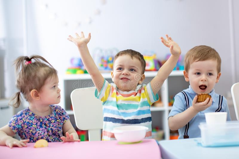 Group of happy kids have a lunch in kindergarten royalty free stock images