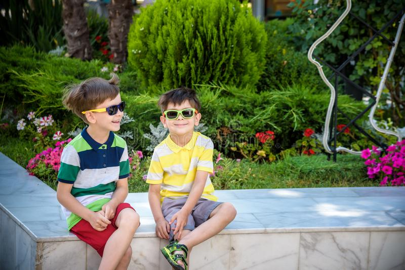 Group of happy children playing outdoors. Kids having fun in park during summer vacation. Friends sitting in sunglasses and royalty free stock images
