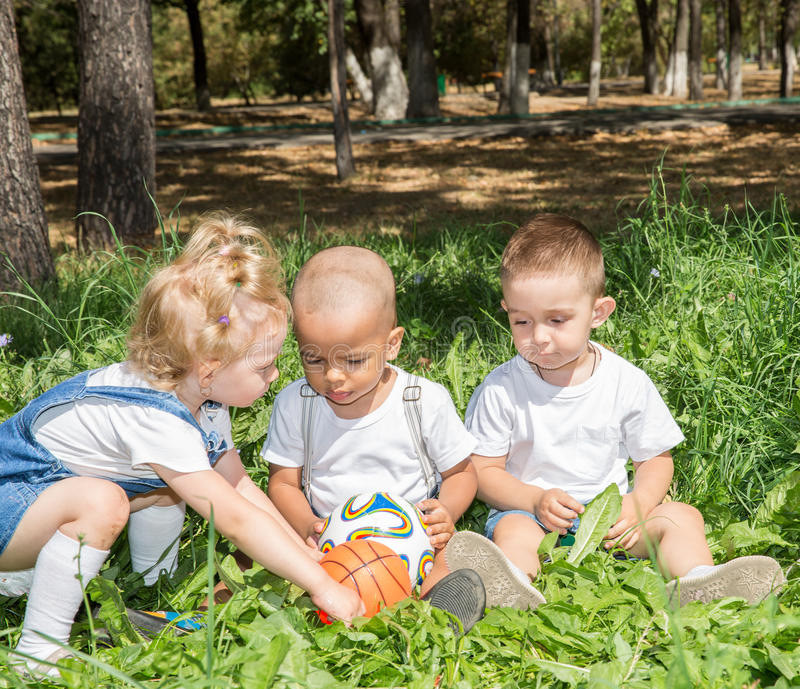 Group of happy children playing with soccer ball in park on nature at summer. Use it for baby and sport concept royalty free stock image