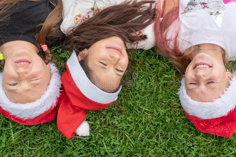 Group of happy children in santa claus hat lies in the park on the green grass and smiling. The concept of a new year, christmas stock photos