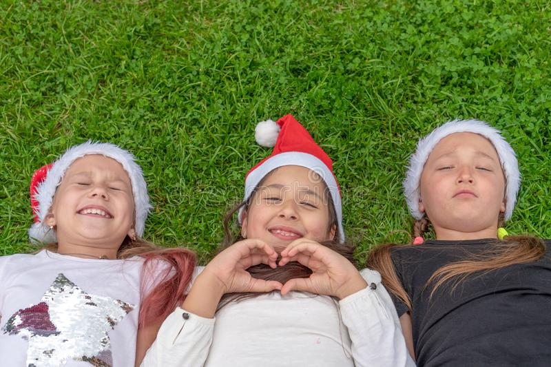 Group of happy children in santa claus hat lies in the park on the green grass and smiling. The concept of a new year, christmas stock photography