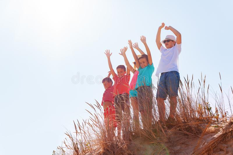 Happy kids boys and girls wave from sand dune stock photography