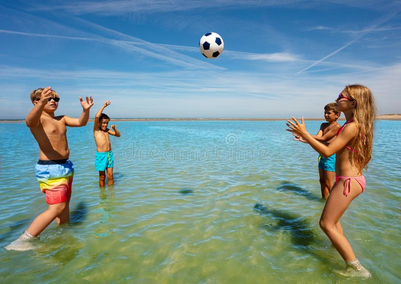 Group of happy cute kids play volleyball in water royalty free stock images