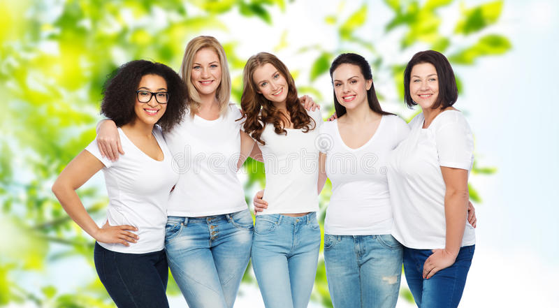 Group of happy different women in white t-shirts. Friendship, diverse, body positive and people concept - group of happy different size women in white t-shirts royalty free stock image