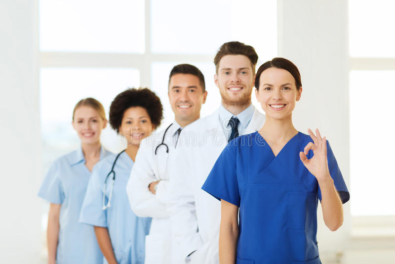 Group of happy doctors at hospital. Hospital, profession, gesture, people and medicine concept - group of happy doctors showing ok hand sign at hospital royalty free stock photos