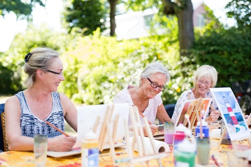 Group of happy elderly women attending an outdoor art class in a garden or park painting from sample pictures on easels while stock images