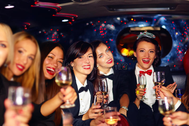 Group of happy elegant women clinking glasses in limousine, hen party. Group of happy elegant women, friends clinking glasses in limousine, hen party royalty free stock photo