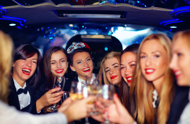 Group of happy elegant women clinking glasses in limousine, hen party. Group of happy elegant women, friends clinking glasses in limousine, hen party stock photography