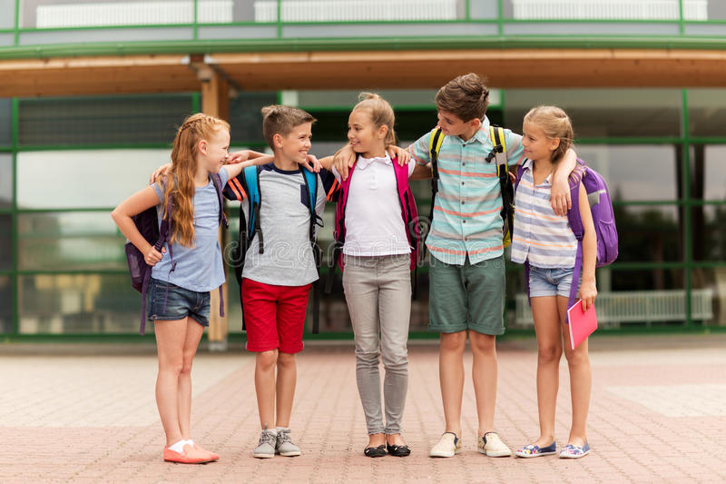 Group of happy elementary school students hugging stock photography