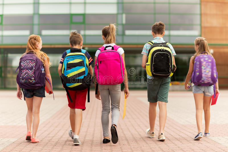 Group of happy elementary school students walking stock image