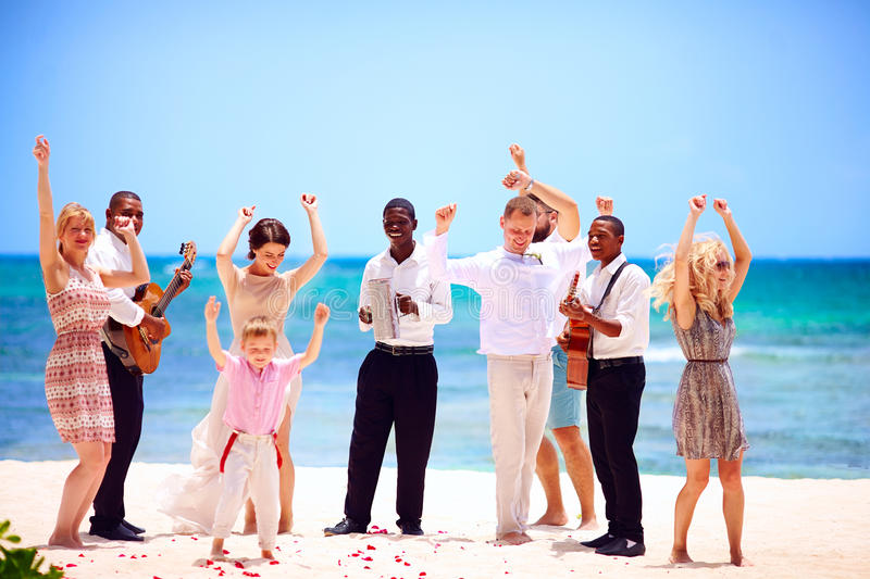 Group of happy family on celebration the exotic wedding with musicians, on tropical beach. Group of happy people, family on celebration the exotic wedding with stock images