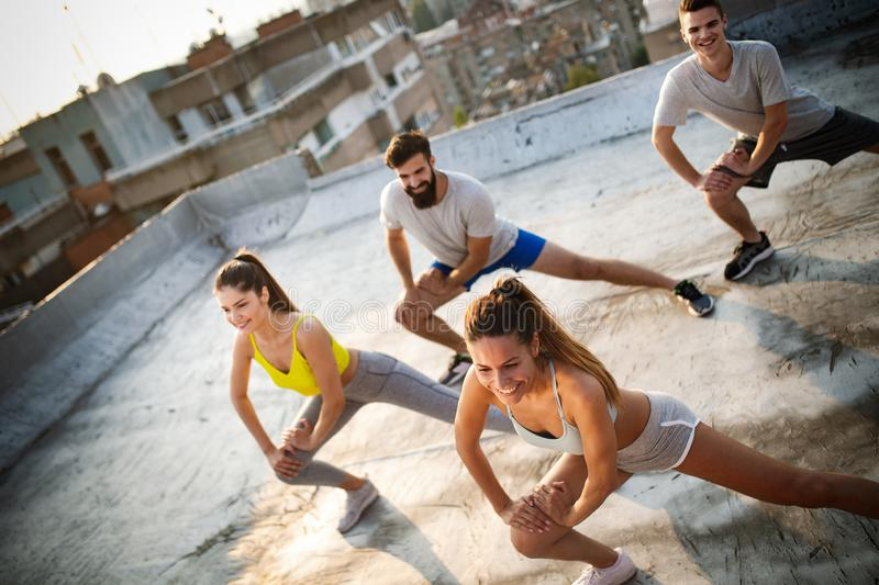 Group of happy fit friends exercising outdoor in city stock photos