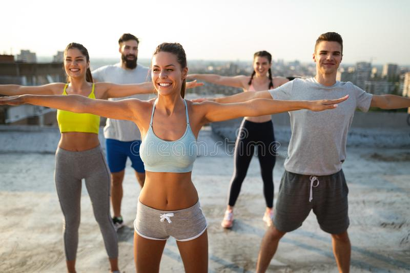 Group of happy fit friends exercising outdoor in city stock images