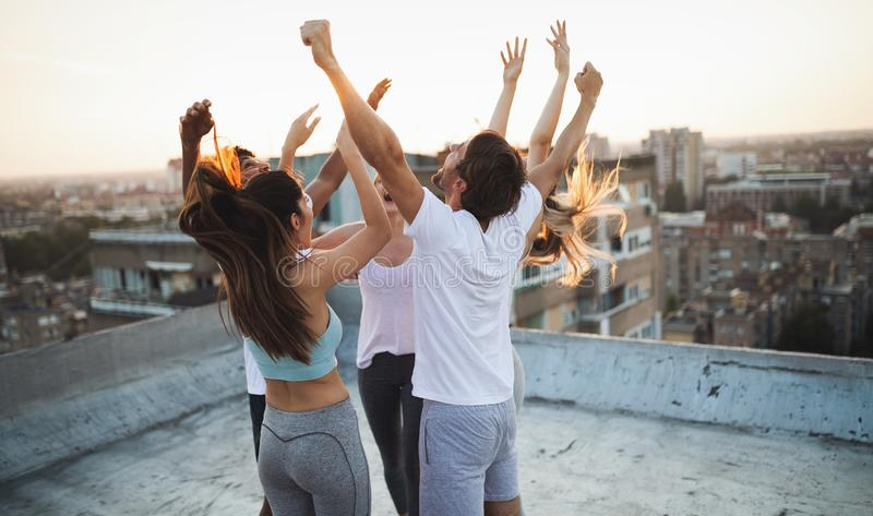 Group of happy fit friends exercising outdoor in city stock photo