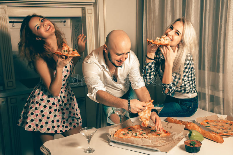 Group of happy freinds enjoying pizza party. Celebrate, disco, party, nightlife, entertainment, friendship concept stock photography