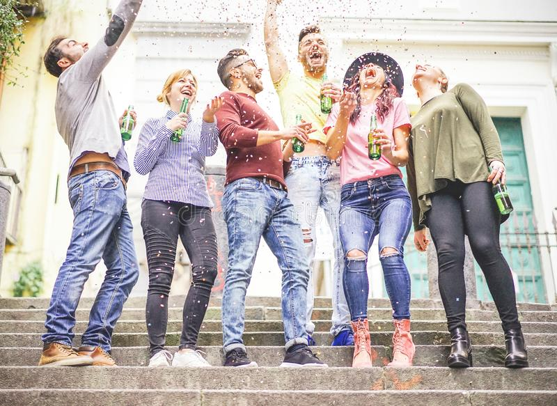 Group of happy friends celebrating together throwing up confetti and drinking beers stock photos