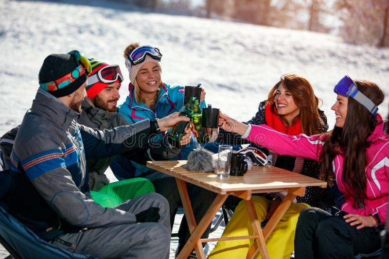 Happy friends cheering with drink after skiing day in cafe at sk stock images
